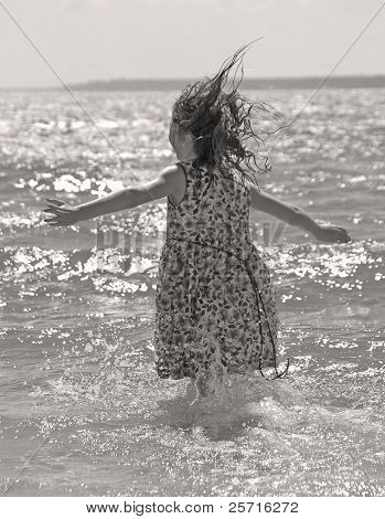 Carefree Young Girl in Fancy Dressing Playing in Ocean Water