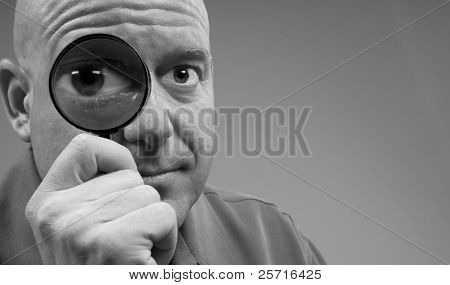Man Looking Through Magnifying Glass with Big Eye for Humorous Effect