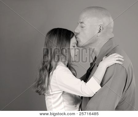 Tender Moment with Father Kissing Daughter on Forehead