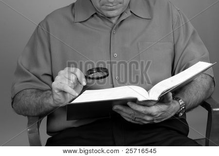 Middle Aged Man Needing Magnifying Glass to Read