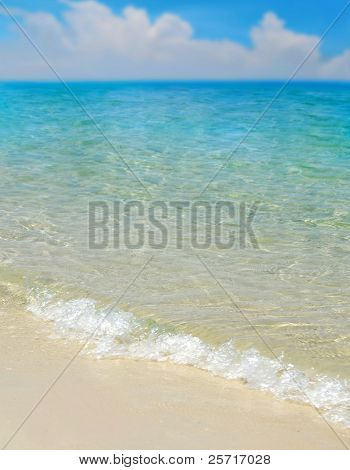 Beautiful turquoise sea and gentle waves with cloudscape in distance