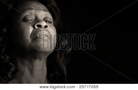 Beautiful middle-aged african american woman shedding tear