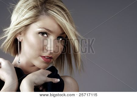Beautiful blonde woman and fancy earrings with hair blowing