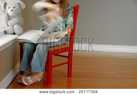 Young girl reading book next to window with her bear