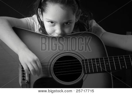 Young Girl Looking Soulful Over Guitar