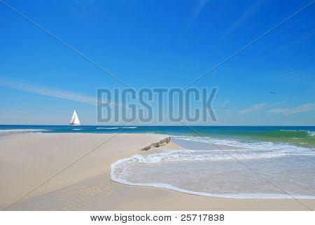 schöne Strand Sand und Dünen mit sanften Wellen mit Segelboot in Ferne unter blauen Himmel