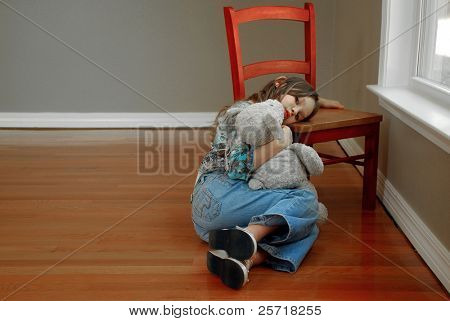 Young girl, holding her bear, looking sad and lonely in room