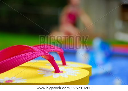 Pretty flip flops next to pool with girl running in distance