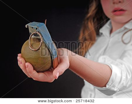 Young child holding military hand grenade