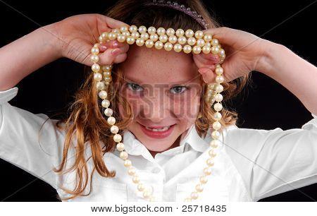 Cute freckle faced girl with missing front teeth playing with mommy's pearl necklace