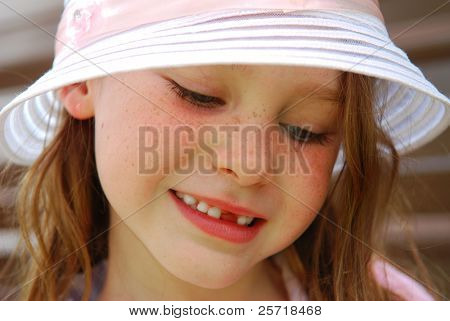 Shy and demure young freckle faced girl wearing pretty hat