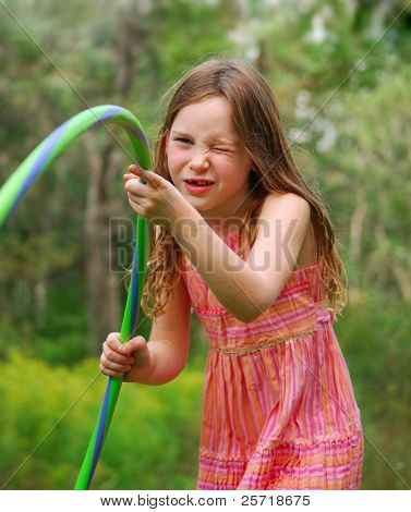 Young girl playing with hula hoop outside
