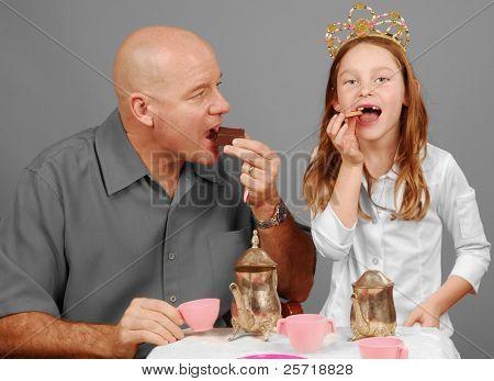 Father enjoying treats at tea party with princess daughter