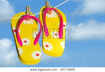 Pretty yellow flip flop sandals on clothes line under pretty sky