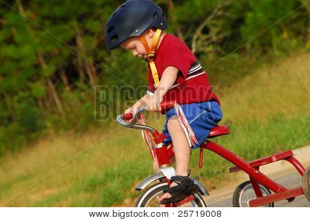 Cute young boy riding tricycle with safety helmet on head
