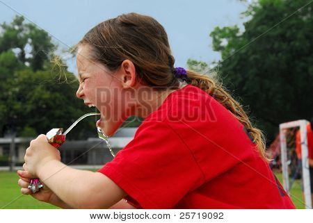 Young soccer playing girl hot and thirsty drinking to rehydrate