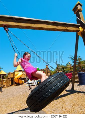 Young girl having fun on tire swing at pretty park