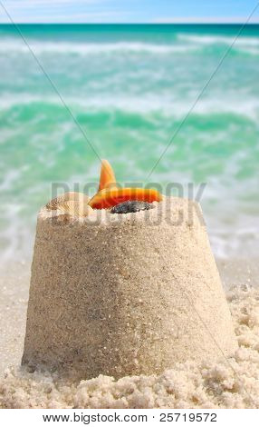 Sandcastle and shells next to pretty ocean