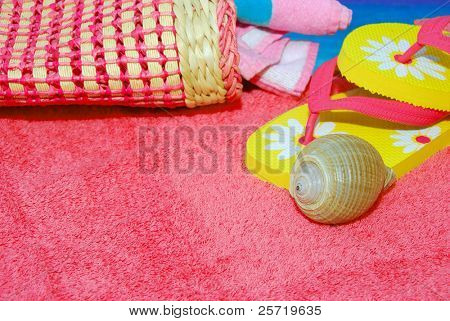 Pretty array of beach accessories on towel next to blue water