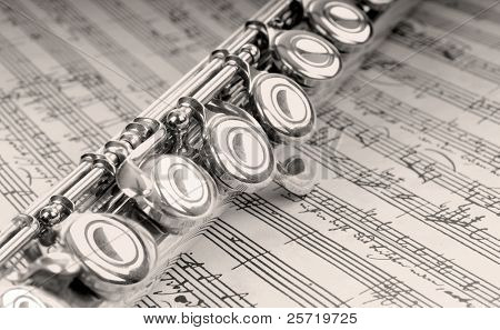 Silver flute instrument resting on handwritten music