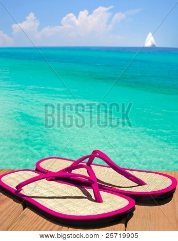 Pink flip flop sandals on dock overlooking gorgeous ocean with sailboat in distance