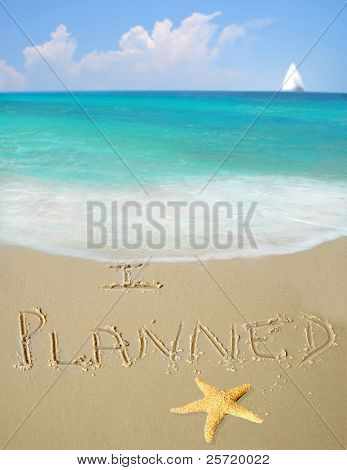 I planned written in sand by gorgeous ocean and starfish with sailboat in distance