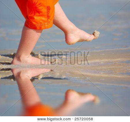 Young child kicking sand by pretty tidepool in beach