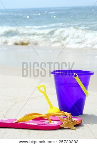 Beach pail, flip flops and starfish on pretty beach
