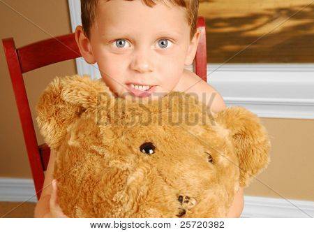 Young boy holding huge bear by window