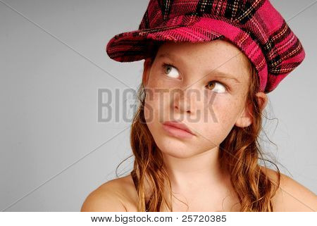 Freckle faced young girl looking up wearing pink plaid cap