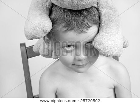 Young boy acting silly with stuffed animal on head