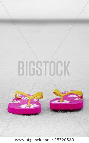 Bright colored flipflops on sand of vast empty coast