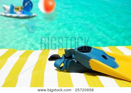 Swimming fins and toys by beach towel and pool