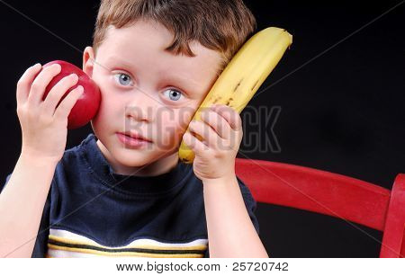 Young boy holding apple and banana