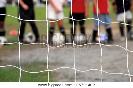 Kid players lined up behind soccer goal at practice