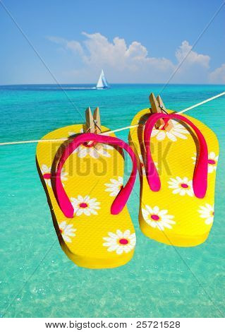 Flip flops at ocean with sailboat in distance