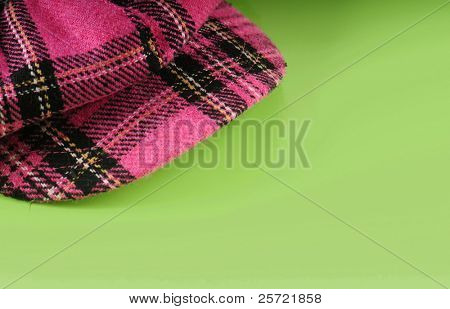 pink plaid cap on green background