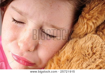 close up of young girl, crying holding bear