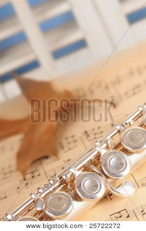 flute on old sheet music by window