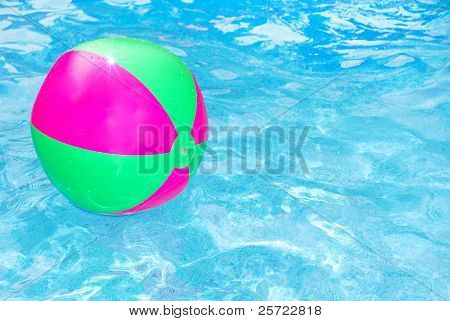 Pretty inflatable beach ball floating in pool