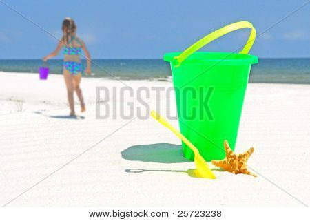 child on beach with bucket by starfish at seashore