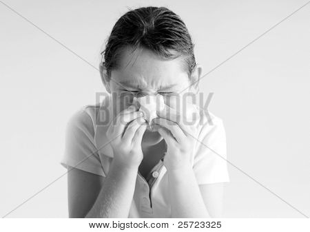 Young girl with tissue blowing nose during cold