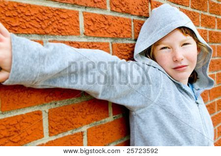 Young girl in hoodie against brick wall