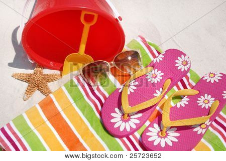 Beach towel, flip flops by bucket and starfish