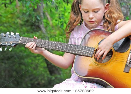 young girl playing guitar outdoors in summer