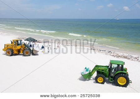 PENSACOLA BEACH - JUNE 23:  BP oil workers using heavy machinery attempt to clean oil covered sand on June 23, 2010 in Pensacola Beach, FL.
