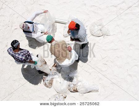 PENSACOLA BEACH - JUNE 23:  BP oil workers bag oil covered sand on June 23, 2010 in Pensacola Beach, FL.