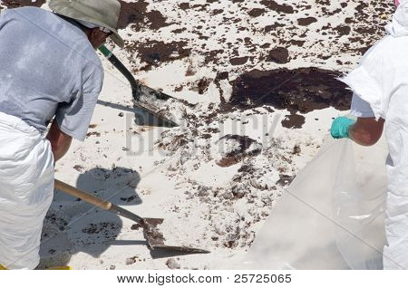 PENSACOLA BEACH - JUNE 23:  A BP oil workers attempt to clean oil  covered sand on June 23, 2010 in Pensacola Beach, FL.
