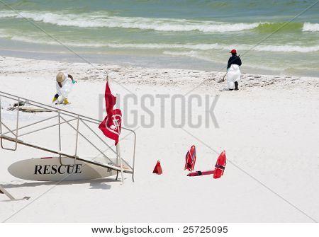 PENSACOLA BEACH - 23 JUNE:  BP oil workers clean oil near a lifeguard stand on June 23, 2010 in Pensacola Beach, FL.
