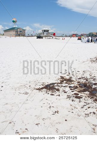 PENSACOLA BEACH - JUNE 23:  A patch of oil is seen on the beach on June 23, 2010 in Pensacola Beach, FL. BP workers can be seen in the distance.